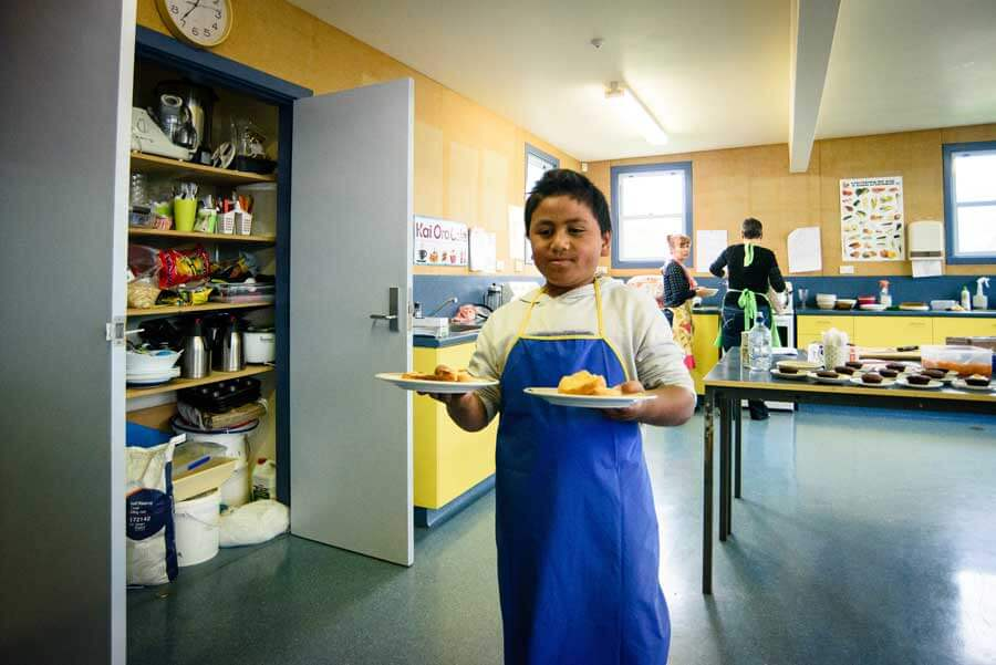 A young boy presents baking he's created. Two people are cooking in the background.